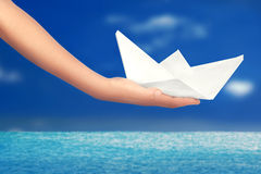 Main tenant un bateau de papier photo stock