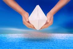 Main tenant un bateau de papier photos stock