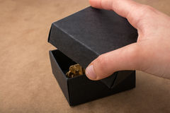Main tenant un boîte-cadeau de couleur noire Photographie stock