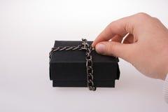 Main tenant un boîte-cadeau de couleur noire Photos libres de droits