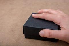 Main tenant un boîte-cadeau de couleur noire Image stock