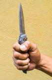Main tenant un couteau sur le fond jaune photographie stock