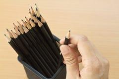 main tenant un crayon de trousse d'écolier Photo libre de droits