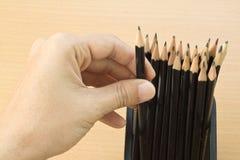 main tenant un crayon de trousse d'écolier Photographie stock