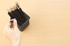 main tenant un crayon de trousse d'écolier Photographie stock libre de droits