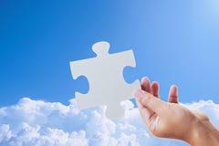 Main tenant un puzzle denteux et un ciel Photo libre de droits