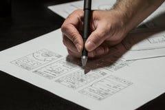 Main tenant un stylo et regardant le projet Image stock