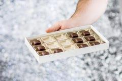 Main tenant une boîte de chocolats Image libre de droits