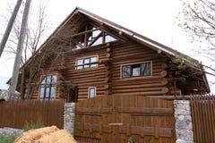 Main tenant une brosse appliquant la peinture de vernis sur un style thaïlandais de maison extérieure en bois photos stock