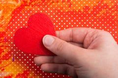 Main tenant une icône en forme de coeur rouge Images stock