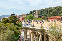 Main terrace, Parc Guell, Barcelona, Spain. Main terrace with its undulating wall and tourists, Parc Guell, Barcelona, Spain, a popular public garden designed by Royalty Free Stock Image
