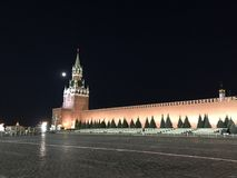 The main tower of the Moscow Kremlin, Russia with huge clock-chimes and a wall of red brick against black night sky and full moon stock photos