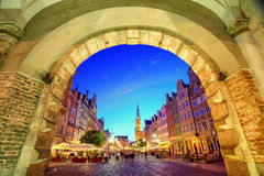 Main Town Hall in the old city of Gdansk, Poland. View of the old town of Gdansk with the Main Town Hall through the arch of Green Gate in the evening, Poland Royalty Free Stock Photography