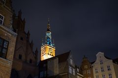 Main Town Hall`s tower in Gdansk at dusk. View of the Main Town Hall`s lit tower and other old buildings in the Main Town Old Town in Gdansk, Poland, in the Stock Image