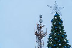 Main tree of the city on the background the tower of the base station communications. During the Christmas holidays people often communicate via phone and Royalty Free Stock Image