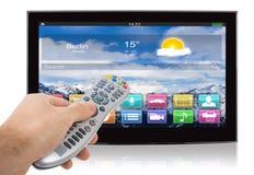 Main utilisant à télécommande de la télévision intelligente d'écran plat Photographie stock libre de droits