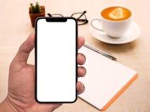 Main utilisant l'écran blanc de smartphone avec l'espace de travail sur la table en bois Photos stock