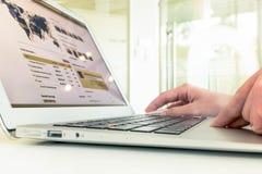 Main utilisant l'ordinateur portable avec l'effet de tache floue Images stock
