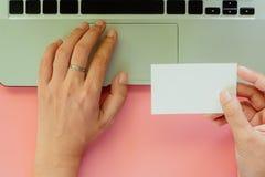 Main utilisant l'ordinateur portable et tenir d'ordinateur les cartes de visite professionnelle vierges de visite sur p photographie stock libre de droits
