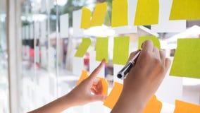 Main utilisant la note collante de post-it avec la séance de réflexion sur le papier de note image stock