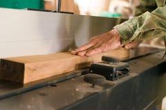 Main utilisant la planeuse électrique et le faisceau en bois Photographie stock