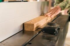 Main utilisant la planeuse électrique et le faisceau en bois Photographie stock libre de droits