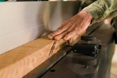 Main utilisant la planeuse électrique et le faisceau en bois Images libres de droits