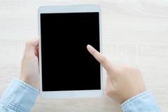 Main utilisant le comprimé avec l'écran vide pour la moquerie au-dessus du backg de table Photographie stock libre de droits
