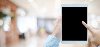Main utilisant le comprimé avec l'écran vide pour la moquerie au-dessus du magasin de tache floue Image libre de droits