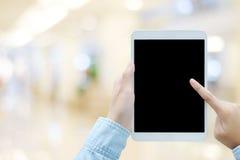Main utilisant le comprimé avec l'écran vide pour la moquerie au-dessus du magasin de tache floue Photographie stock libre de droits