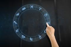 Main utilisant le panneau interactif avec des signes de zodiaque image stock