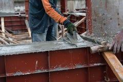 main utilisant lisse le laïus de ciment avec la truelle images stock