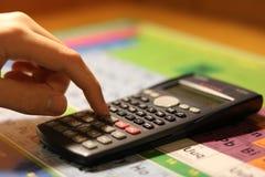 Main utilisant une calculatrice au-dessus d'une table périodique Photos stock