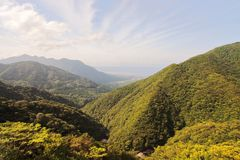 Main view of the northern massive green mountains and seaside of Yakushima Island with city of Miyanoura on background Royalty Free Stock Photo