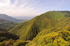 Main view of the northern massive green mountains and seaside of Yakushima Island with city of Miyanoura on background Stock Images
