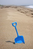Maine Atlantic Beach and Toy. Blue toy shovel in sand at Atlantic ocean beach shore with rocky coast in background. Vertical format Royalty Free Stock Photo
