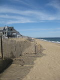 Maine Beach. The beach in maine with the views of the waves and shoreline. The fence line with it's shadows and buildings dotting the shore. The horizon with the Royalty Free Stock Photo