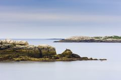 Maine rocky coast line with smooth ocean and blue sky stock image