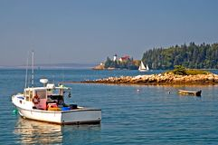Maine scenic coastline. A beautiful and scenic view of a Maine lobster boat anchored in the harbor with a sailboat and lighthouse in the background.  Swan's Royalty Free Stock Photo