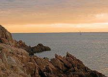 Maine seacoast at dawn. Rocky Maine seacoast at dawn with a sailboat entering the harbor in the distance stock image