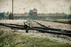 Maingate και σιδηρόδρομος στο ναζιστικό στρατόπεδο συγκέντρωσης Auschwitz Birkenau Η επίδραση με το υπόβαθρο grunge, επινοεί την  στοκ φωτογραφία