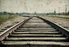 Maingate και σιδηρόδρομος στο ναζιστικό στρατόπεδο συγκέντρωσης Auschwitz Birkenau Η επίδραση με το υπόβαθρο grunge, επινοεί την  στοκ φωτογραφίες
