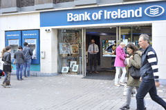 Mainguard Street, Galway, Ireland June 2017, Bank of Ireland ,pe. Ople queuing at the cashier, banker in the door , girl leaving and some people walking around Royalty Free Stock Image