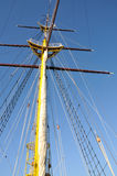 Mainmast of big sailboat with blue sky in background Stock Image