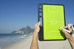 Mains écrivant sur le conseil Rio Beach Brazil de la tactique du football Image libre de droits