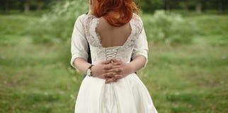 Mains étreignant le marié de jeune mariée avec la vue arrière de cheveux rouges dans la forêt verte Images libres de droits