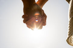 Mains étreintes contre une fusée lumineuse du soleil Photos libres de droits