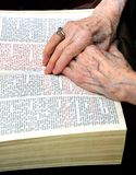 Mains étreintes sur la bible image stock