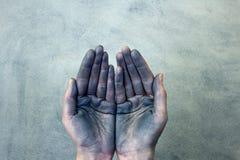 Mains évasées sales tenant quelque chose sur le fond gris photo libre de droits