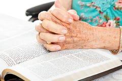 Mains aînées de prière sur la bible Photographie stock libre de droits